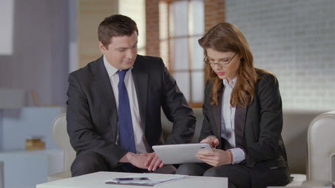 Sales manager shows charts to business client on tablet, slow-mo Footage