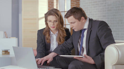 Business lady and man check presentation on laptop, slow motion ภาพวิดีโอ
