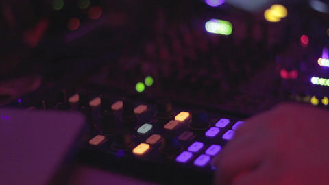 Disc jockey pressing buttons, tweaking mixer controls, nightclub Footage