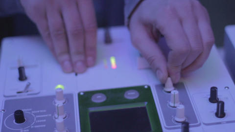 Female disc jockey hand switching, turning controls on turntable Footage
