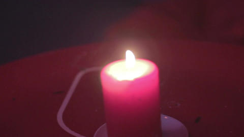 Blurred red candle burning, dark background, romance symbol Footage