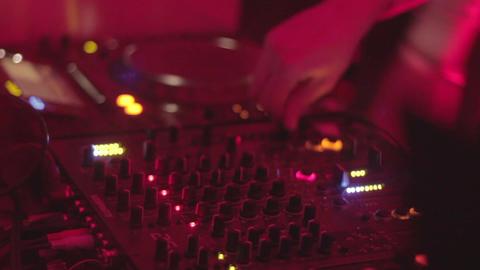 DJ playing records, mixing tracks, turning controls, nightclub Footage