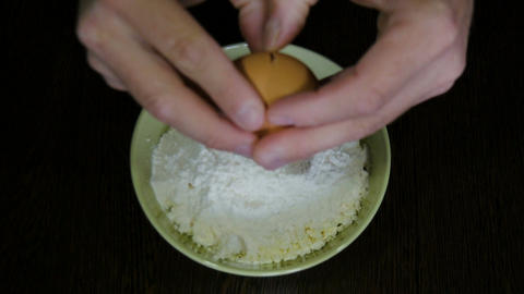 The cook breaks egg in a flour Footage