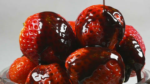 Delicious melted chocolate syrup pouring over strawberries in reverse Footage