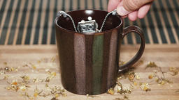 Vintage-grainy style slow motion images of man preparing chamomile tea - putting Footage