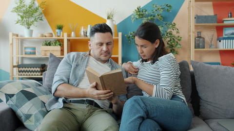 Young couple man and woman reading book talking enjoying literature in apartment Live Action