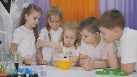 Chemical experiments for children. Children pour reagents into a yellow bowl. Room is filled with Live Action