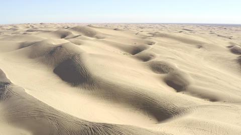 All terrain vehicle ATV tracks on sand dunes in vast desert, aerial view Live Action