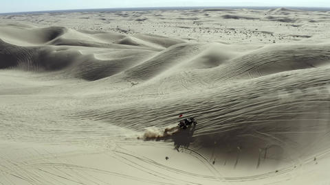 All terrain vehicle ATV driving over sand dunes in desert, aerial view Live Action