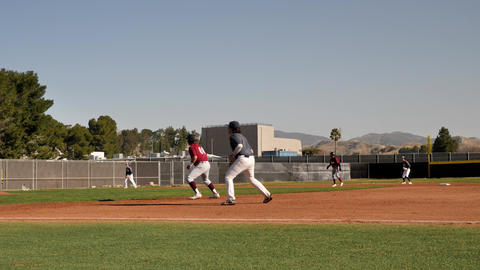 Two high school teams play baseball game on school grounds. Slow motion Live Action
