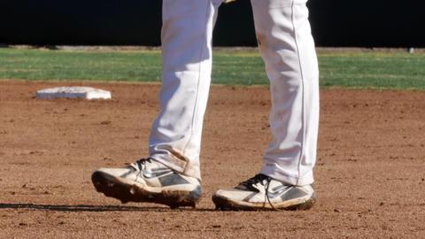 Legs of a baseball player walking on field, wearing Nike footwear shoes Live Action