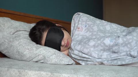 A young woman sleeps in a sleep mask. A girl lies in bed in his room Live Action