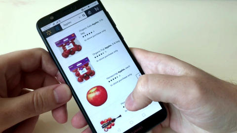A man orders apples in an online store using a smartphone. The choice of Live Action