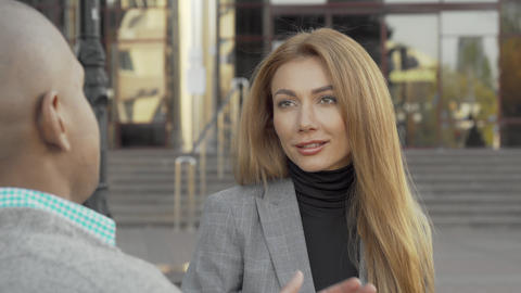 Attractive young businesswoman talking to her colleague outdoors Live Action