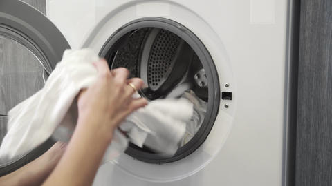 Female hand takes white clothes from laundry machine. Loading washing machine Live Action