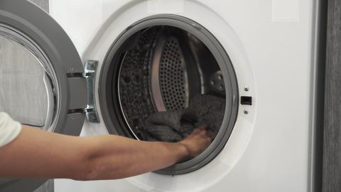 Female hand takes GREY SWEATER from laundry machine. Loading washing machine Live Action