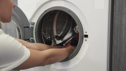 Female hand takes COLORED CLOTHES from laundry machine. Loading washing machine Live Action