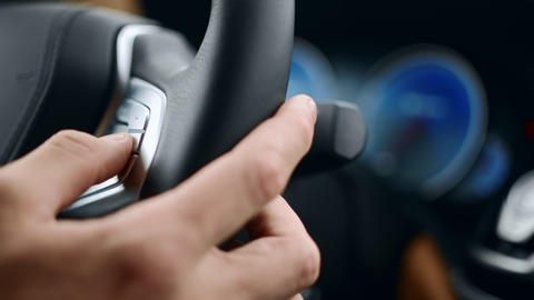 Close up male hand pushing buttons on wheel. Man fingers touching buttons in car Live Action