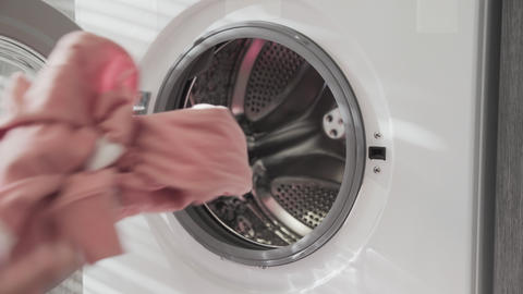 Female hand puts PINK CLOTHES in laundry machine. Loading washing machine. Load Live Action