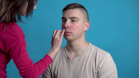Make-up is applied to a young man. The girl applies makeup to a man before Live Action