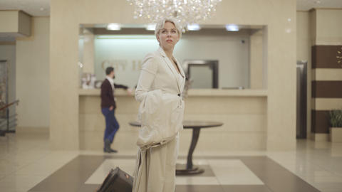 Portrait of young blond Caucasian woman looking around in luxurious vestibule Live Action