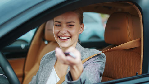 Closeup smiling woman sitting in new car. Happy woman getting keys from new car Live Action