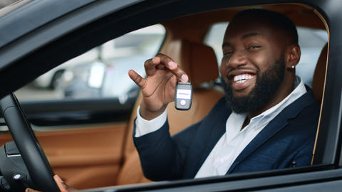Closeup businessman shaking key in new car. African man smiling in vehicle Live Action