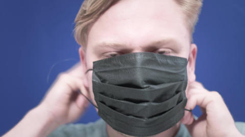 portrait of a young man putting a medical mask on his face. Concept of health Live Action