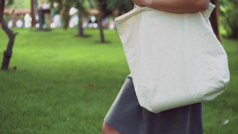 Young girl holds white textile eco bag and walks in the summer park Live Action