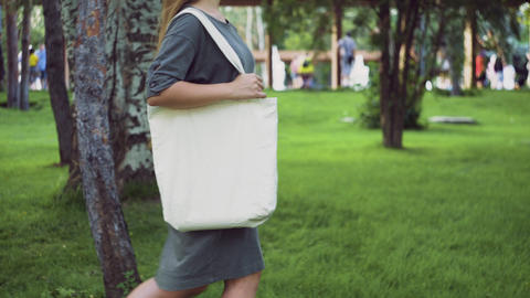 Side view of Young girl holds white textile eco bag and walks in the summer park Live Action