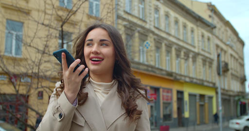Woman using a smartphone voice recording function online in the city street Live Action
