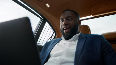 Portrait of surprised african american man getting good news at luxury car Live Action
