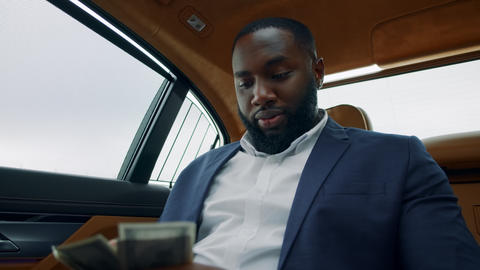 Portrait of businessman counting money at car. African guy smelling money at car Live Action
