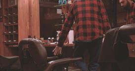 Lumberjack sits down barber chair barbershop 4k video. Bearded man in salon Filmmaterial