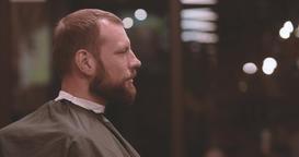 Smiling lumberjack style bearded man seat in barbershop HD video. Hairstyling Footage