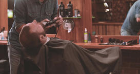 Barber cutting beard with clipper at barbershop 4k video. Styling electric razor Footage