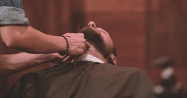 Barber cutting beard with clipper at barbershop 4k close-up video. Styling Footage