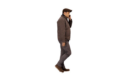Side view of a man walking & talking on a mobile phone, 4k shot alpha channel Footage