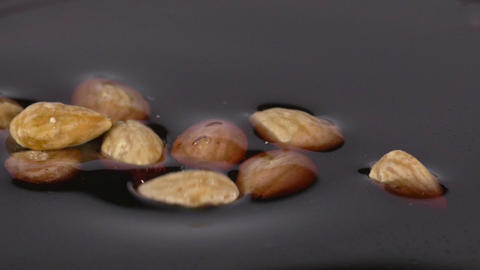 Close-up of delicious roasted almonds falling into chocolate syrup Footage