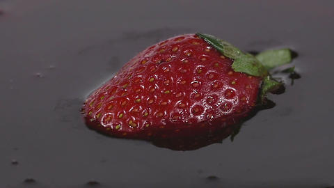 Close-up of delicious strawberry falling into chocolate syrup Footage