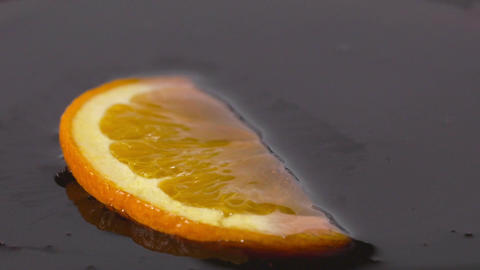 Close-up of a delicious orange slice falling into chocolate syrup Footage