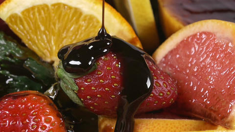 Pouring chocolate syrup over a plate with fruit in slow motion Footage