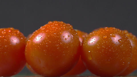 Close-up of cherry tomatoes sprinkled with water and rotating on a plate Footage