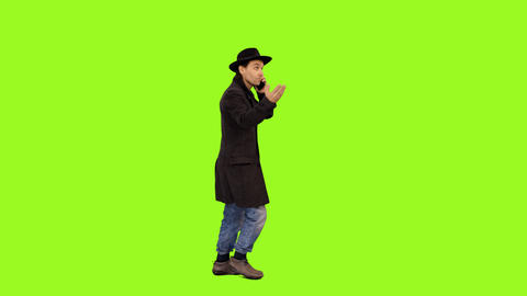 Side view of a man walking & talking on smartphone, alpha channel Footage