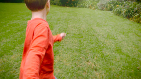 A young boy leading and pulling someone while running through the grass - slowmo Footage