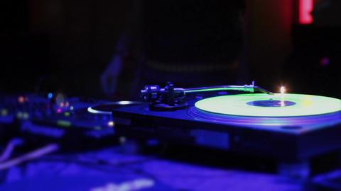 Vinyl record rotating on turntable, DJ at work, strobe light Footage