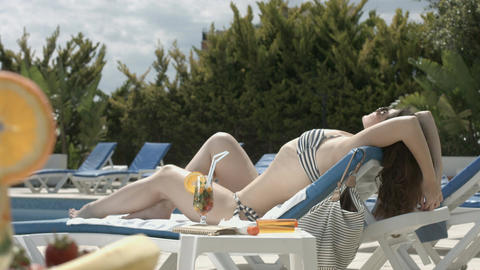 Attractive young female suntanning near swimming pool, vacation Footage
