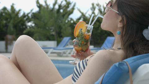 Young relaxed lady drinking cocktail on beach, enjoying vacation Footage
