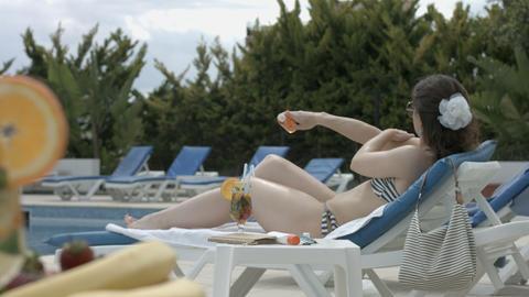 Brunette model taking care of skin with sun cream, having rest Footage