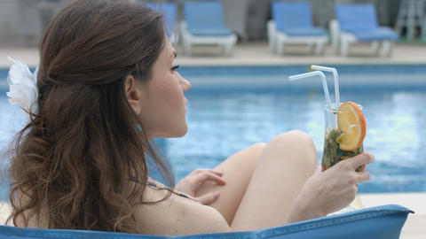Pretty female drinking fresh cocktail near pool at summer resort Footage